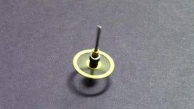 Cog wheel spinning. Metallic cog wheel spinning until losing equilibrium on flat surface stock video footage