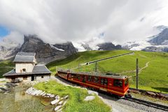 Cog wheel train traveling on Jungfrau Railway from Jungfraujoch station top of Europe to Kleine Scheidegg. On a green hillside with a snow shed tunnel on a royalty free stock images