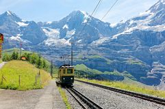 A cog wheel train traveling on the mountain Railway from Wengen to Kleine Scheidegg station. With majestic Swiss Alps Eiger, Monch, Jungfrau in background, in stock photography