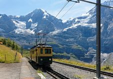 A cog wheel train traveling on the mountain Railway from Wengen to Kleine Scheidegg station. With majestic Swiss Alps Eiger, Monch, Jungfrau in background, in stock image