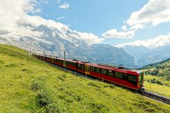 A cog wheel train travels on famous Jungfrau Railway from Kleine Scheidegg to Jungfraujoch station Royalty Free Stock Images