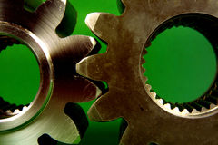 Cog wheels idea. Two large cog-wheels against green Stock Image