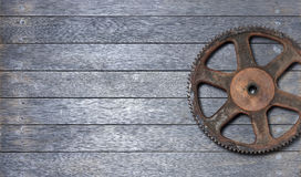 Cog Wood Background. One large rusty cog on a wood background Stock Image