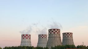 Cogeneration power plant in city. Thermal Power Station chimney smoke sky. Sunset landscape. Combined heat and power. Plant near megapolis. Chimney-stalk and stock footage