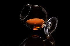 Cognac. Inclined glass of cognac on black background Stock Photos