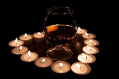 Cognac. Valentine's Day composition with one glass of cognac in the center of candle burn heart stock photos