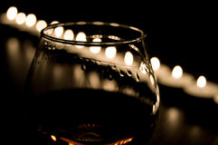 Cognac. One glass of cognac in the candle burn stock photos