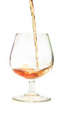 Cognac. Pour in a beautiful wine glass. Isolation on white Stock Photo