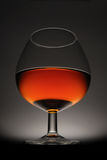 Cognac. Glass of cognac on a black background Stock Photos