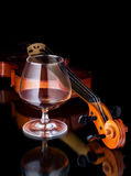 Cognac. Snifter glass of cognac and violin Royalty Free Stock Images