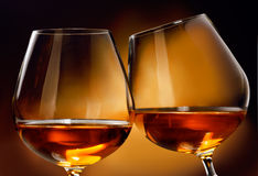 Cognac or Brandy. To clink two glasses of Cognac or Brandy liquor in front of a brownish background Stock Photos