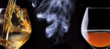 Cognac or brandy on a black with cigar smoke Royalty Free Stock Image