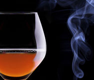 Cognac or brandy on a black with cigar smoke Stock Image