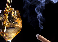 Cognac or brandy on a black with cigar smoke Royalty Free Stock Photography