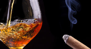 Cognac or brandy on a black with cigar smoke Royalty Free Stock Photo