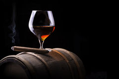 Cognac and Cigar on black with vintage barrel. Cognac and Cigar on black background with wooden vintage barrel Stock Image