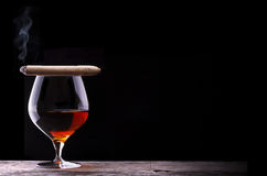 Cognac and Cigar on black with vintage table Stock Photography