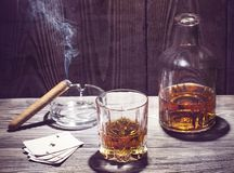 Cognac and cigar burning on a wooden table Stock Photos