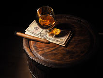 Cognac ,Cigar and dollars on old oak barrel Royalty Free Stock Photos