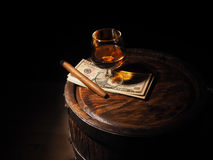Cognac ,Cigar and dollars on old oak barrel Royalty Free Stock Images