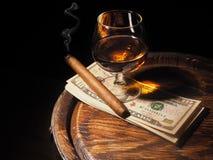 Cognac ,Cigar and dollars on old oak barrel Royalty Free Stock Image