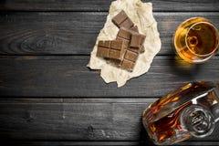 Cognac con i pezzi di cioccolato amaro fotografia stock
