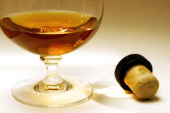 Cognac and cork. Glass of cognac and a cork Royalty Free Stock Photos