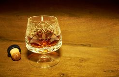 Cognac in a crystal glass. Set on stained wood royalty free stock images