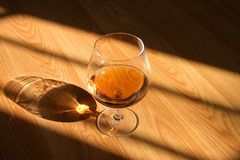 Cognac drink. A glass of cognac on a wooden floor Stock Photography
