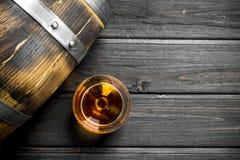 Cognac in een glas met een vat stock afbeelding