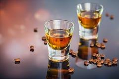 Cognac eller likör, kaffebönor och kryddor på en glass tabell arkivfoton