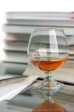 Cognac en boeken Stock Foto