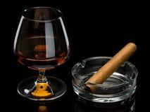 Cognac et cigare dans un cendrier en verre Photo libre de droits