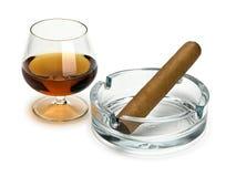 Cognac et cigare dans un cendrier en verre Photo stock