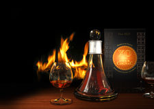 Cognac and Fireplace. Rendering of a carafe and glasses filled with old cognac XO with a fireplace in the background Stock Photos