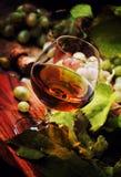 Cognac in Glas, Wijndruiven en Wijnstok, Uitstekende Houten Achtergrond, stock foto's