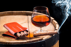 Cognac in a glass on barrel and burning cigar Royalty Free Stock Photo