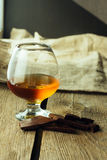 Cognac glass and chocolate Royalty Free Stock Photos