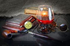 Cognac glass in an environment old, a retro of things. Still life with a cognac glass, hours, a tube for smoking, ancient books, points and a fountain pen in a Royalty Free Stock Photography