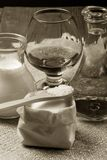 Cognac in a glass goblet, milk, water, sugar and salt in wooden Stock Photos