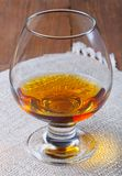 Cognac in a glass goblet on the old wooden table and linen napki Royalty Free Stock Photos