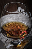 Cognac in a glass goblet on the old wooden table and linen napki Royalty Free Stock Photo