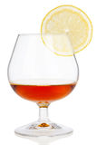 Cognac glass with lemon  on white Stock Photography
