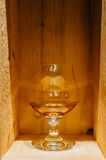 Cognac glass with nice wooden background Stock Images