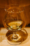 Cognac glass with nice wooden background Royalty Free Stock Images