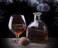 Cognac glass shrouded in a smoke Stock Image