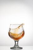 Cognac glass with splash Stock Image