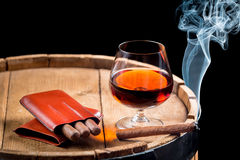 Cognac in a glass on wooden barrel Royalty Free Stock Image