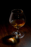 Cognac glass on a wooden table Stock Image