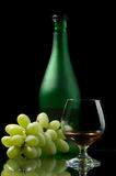 Cognac and grapes. Glass excellent brandy on a dark background Stock Photo